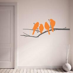 Primer izgleda sive in oranžne samolepilne stenske nalepke Ptički na veji na beli steni v dnevni sobi.