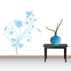 Primer izgleda svetlo modre samolepilne stenske nalepke Roža s tremi cveti na beli steni v dnevni sobi.
