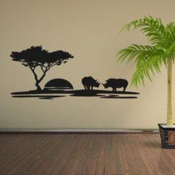 Primer izgleda črne samolepilne stenske nalepke Safari nosoroga na bež steni v dnevni sobi.