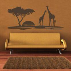 Primer izgleda čokoladno rjave samolepilne stenske nalepke Safari žirafi na rjava steni v dnevni sobi.