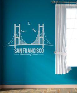 Primer izgleda bele samolepilne stenske nalepke San Francisco Brigde na modri steni v dnevni sobi. Na nalepki piše: San Francisco, United State of America