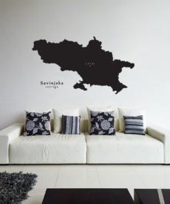 Primer izgleda črne samolepilne stenske nalepke Savinjska na beli steni v dnevni sobi.