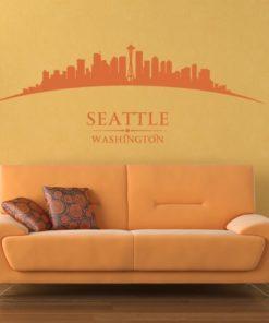 Primer izgleda oranžne samolepilne stenske nalepke Seattle ukrivljen na rumeni steni v spalnici. Na nalepki piše: Seattle, Washington