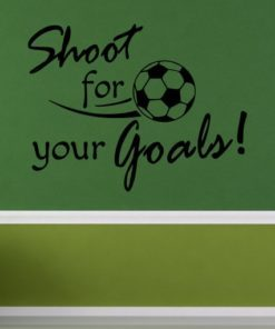 Primer izgleda črne samolepilne stenske nalepke Shoot for your Goals na zeleni steni v otroški sobi. Nalepka je napis, ki se glasi: Shoot for your Goals!