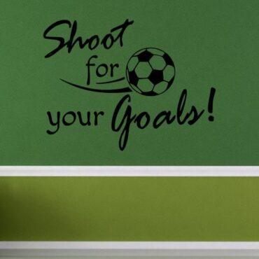 Primer izgleda črne samolepilne stenske nalepke Shoot for your Goals na zeleni steni v otroški sobi. Nalepka je napis, ki se glasi: Shoot for your Goals!
