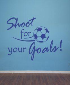 Primer izgleda modre samolepilne stenske nalepke Shoot for your Goals na modra steni v otroški sobi. Nalepka je napis, ki se glasi: Shoot for your Goals.