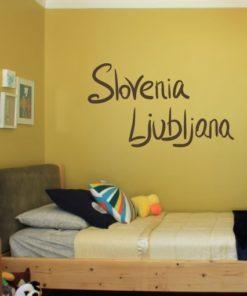 Primer izgleda čokoladno rjave samolepilne stenske nalepke Slovenia Ljubljana pisano na rumeni steni v otroški sobi.
