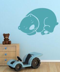Primer izgleda zelene samolepilne stenske nalepke Speči medo na modri steni v otroški sobi.