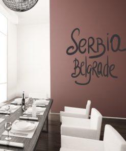 Primer izgleda črne samolepilne stenske nalepke Beograd Pisano na rjavi steni v jedilnici.