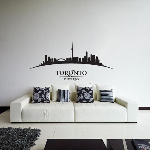 Primer izgleda črne samolepilne stenske nalepke Toronto ukrivljen na beli steni v dnevni sobi. Na nalepki piše: Toronto, Ontario