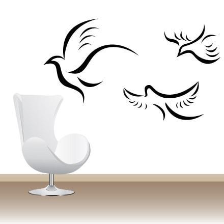 Primer izgleda črne samolepilne stenske nalepke Tri črtaste ptice na beli steni v dnevni sobi.