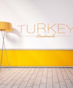 Primer izgleda oranžne samolepilne stenske nalepke Turčija napis na beli steni v dnevni sobi.