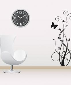 Primer izgleda črne samolepilne stenske nalepke Valovita trava z metuljem na beli steni v dnevni sobi.