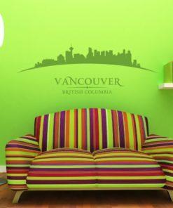 Primer izgleda zelene samolepilne stenske nalepke Vancouver ukrivljen na zeleni steni nad zofo v dnevni sobi. Na nalepki piše: Vancouver, British Columbia