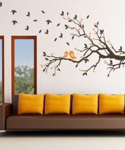 Primer izgleda čokoladno rjave in oranžne samolepilne stenske nalepke Veje v jeseni na beli steni v dnevni sobi.