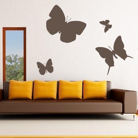 Primer izgleda čokoladno rjave samolepilne stenske nalepke Veliki metuji na beli steni v dnevni sobi.