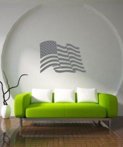 Primer izgleda grafitno sive samolepilne stenske nalepke ZDA zastava na beli steni nad zofo v dnevni sobi.