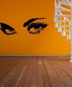 Primer izgleda črne samolepilne stenske nalepke Zapeljive oči na oranžni steni.