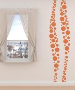 Primer izgleda oranžne samolepilne stenske nalepke Zavit pas iz krogcev na beli steni.