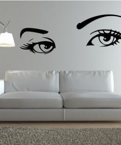 Primer izgleda črne samolepilne stenske nalepke Ženske oči na steni bele barve v dnevni sobi.